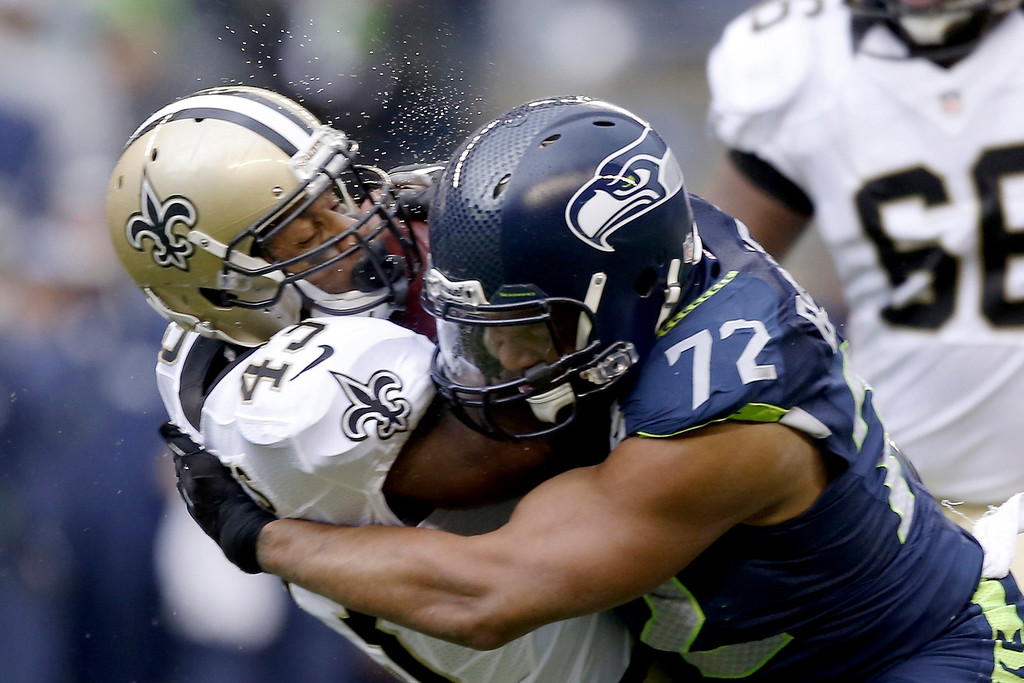 . SEATTLE, WA - JANUARY 11:  Running back Darren Sproles #43 of the New Orleans Saints is hit by defensive end Michael Bennett #72 of the Seattle Seahawks in the first half during the NFC Divisional Playoff Game at CenturyLink Field on January 11, 2014 in Seattle, Washington.  (Photo by Otto Greule Jr/Getty Images)