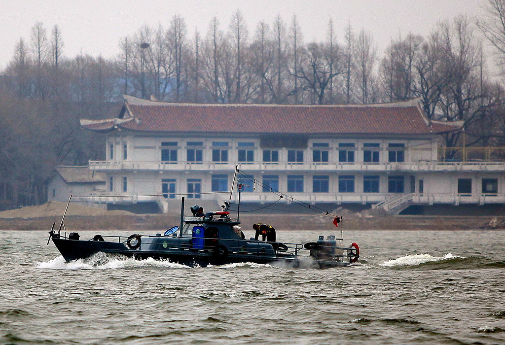 """. A North Korean boat makes its way along the Yalu River by the North Korean town of Sinuiju across from the Chinese city of Dandong on March 31, 2013. North Korea on March 30 declared it was in a \""""state of war\"""" with South Korea and warned Seoul and Washington that any provocation would swiftly escalate into an all-out nuclear conflict.      CHINA OUT      AFP PHOTO        (Photo credit should read STR/AFP/Getty Images)"""