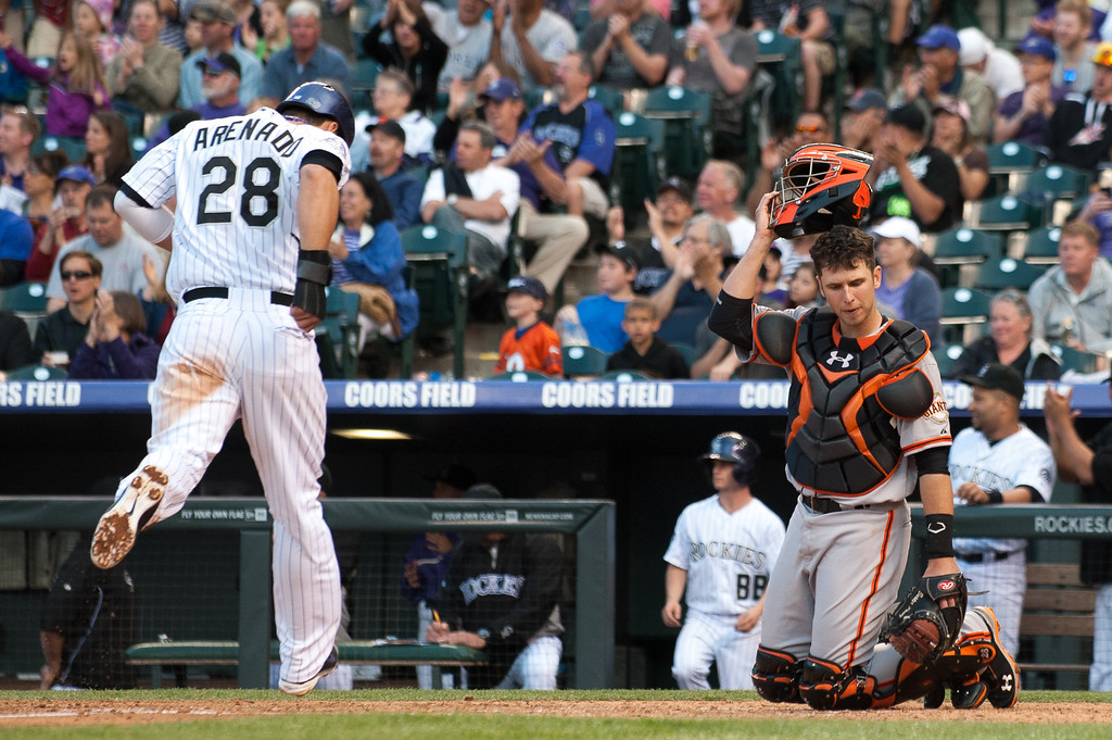 . DENVER, CO - MAY 18:  Buster Posey #28 of the San Francisco Giants reacts as Nolan Arenado #28 of the Colorado Rockies touches home plate for the third run in the bottom of the third inning of a game between the Colorado Rockies and the San Francisco Giants at Coors Field on May 18, 2013 in Denver, Colorado. The Rockies led the Giants 4-1 after four innings.  (Photo by Dustin Bradford/Getty Images)