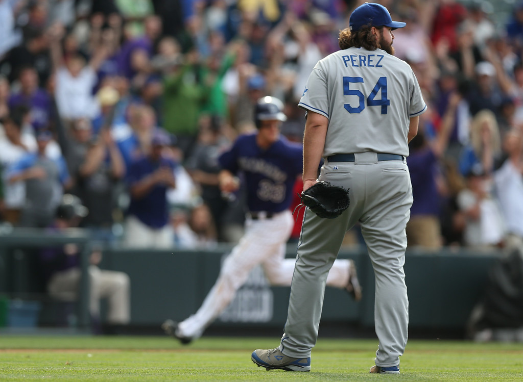 . Los Angeles Dodgers relief pitcher Chris Perez, front, turns to watch the game-winning hit fall in the outfield as Colorado Rockies base runner Justin Morneau, back, rounds third base to score the winning run in the 10th inning of the Rockies\' 5-4 victory in 10 innings in a baseball game in Denver on Saturday, June 7, 2014. (AP Photo/David Zalubowski)