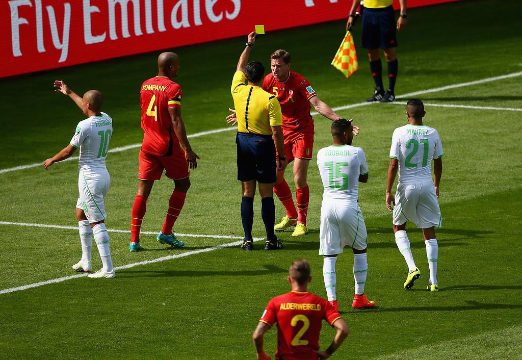. BELO HORIZONTE, BRAZIL - JUNE 17: Jan Vertonghen of Belgium is shown a yellow card by referee Marco Rodriquez after a foul on Sofiane Feghouli of Algeria (L) resulting in a penalty kick during the 2014 FIFA World Cup Brazil Group H match between Belgium and Algeria at Estadio Mineirao on June 17, 2014 in Belo Horizonte, Brazil.  (Photo by Quinn Rooney/Getty Images)