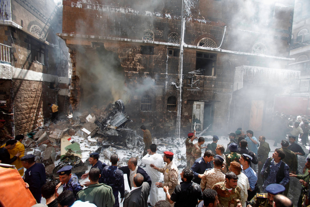 Description of . Military personnel and people gather at the site of a military aircraft crash in Sanaa February 19, 2013.  A Yemeni fighter jet crashed in the centre of the capital Sanaa on Tuesday, killing at least six people, medical sources said.  REUTERS/Khaled Abdullah