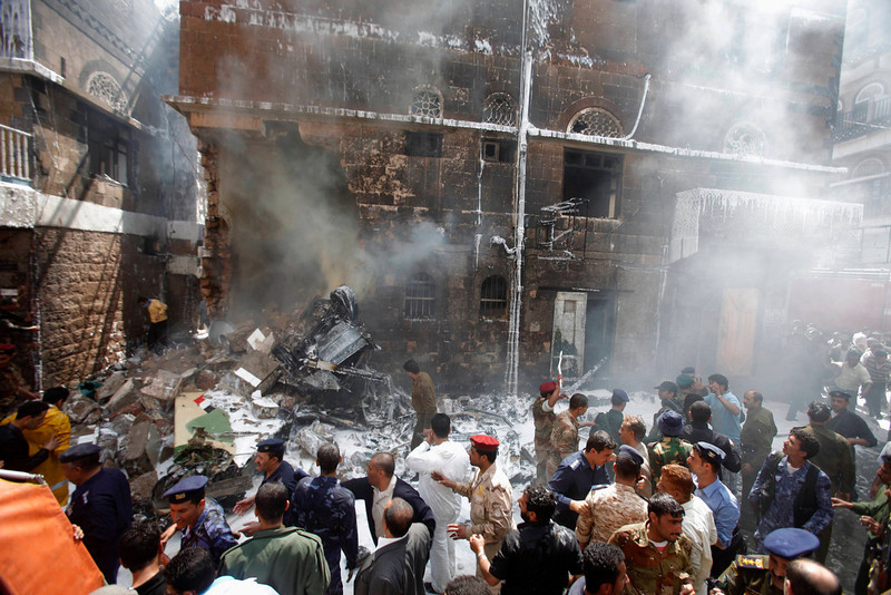 . Military personnel and people gather at the site of a military aircraft crash in Sanaa February 19, 2013.  A Yemeni fighter jet crashed in the centre of the capital Sanaa on Tuesday, killing at least six people, medical sources said.  REUTERS/Khaled Abdullah