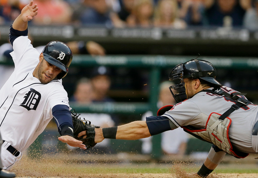 . Cleveland Indians catcher Yan Gomes tags out Detroit Tigers\' J.D. Martinez who was attempting to score from first on a double by teammate Torii Hunter during the fourth inning of a baseball game in Detroit, Friday, July 18, 2014. (AP Photo/Carlos Osorio)