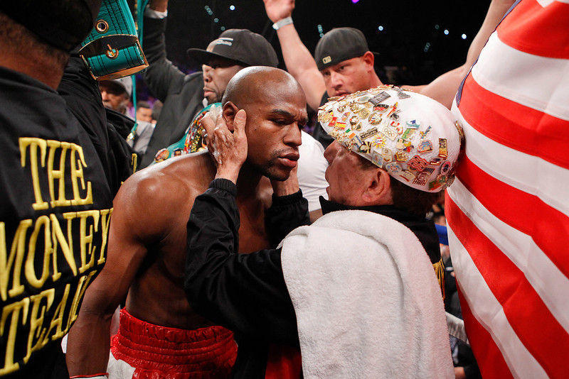 . Floyd Mayweather Jr., left, gets some last minute instructions from his trainer before fighting Miguel Cotto for the WBA super welterweight title, Saturday, May 5, 2012, in Las Vegas.  (AP Photo/Eric Jamison)