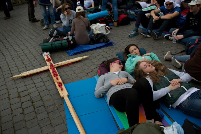 . Pilgrims rest in St. Peter\'s Square at the Vatican, Saturday, April 26, 2014. Pilgrims and faithful are gathering in Rome to attend Sunday\'s ceremony at the Vatican where Pope Francis will elevate in a solemn ceremony John XXIII and John Paul II to sainthood. (AP Photo/Emilio Morenatti)