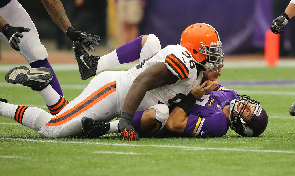 . Christian Ponder #7 of the Minnesota Vikings reacts to a tackle by Phillip Taylor #98 of the Cleveland Browns on September 22, 2013 at Mall of America Field at the Hubert Humphrey Metrodome in Minneapolis, Minnesota. (Photo by Adam Bettcher/Getty Images)