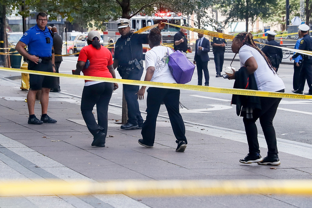 . Pedestrians are allowed to exit police cordons as emergency personnel and police work the scene of shooting near Fountain Square, Thursday, Sept. 6, 2018, in downtown Cincinnati. (AP Photo/John Minchillo)