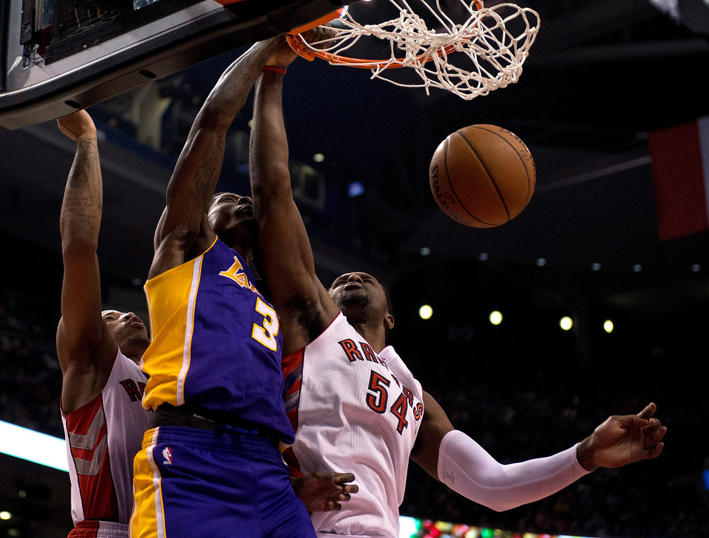 . Los Angeles Lakers guard Manny Harris (3) slams home a dunk between Toronto Raptors guard DeMar DeRozan, left, and forward Patrick Patterson (54) during first-half NBA basketball game action in Toronto, Sunday, Jan. 19, 2014. (AP Photo/The Canadian Press, Frank Gunn)