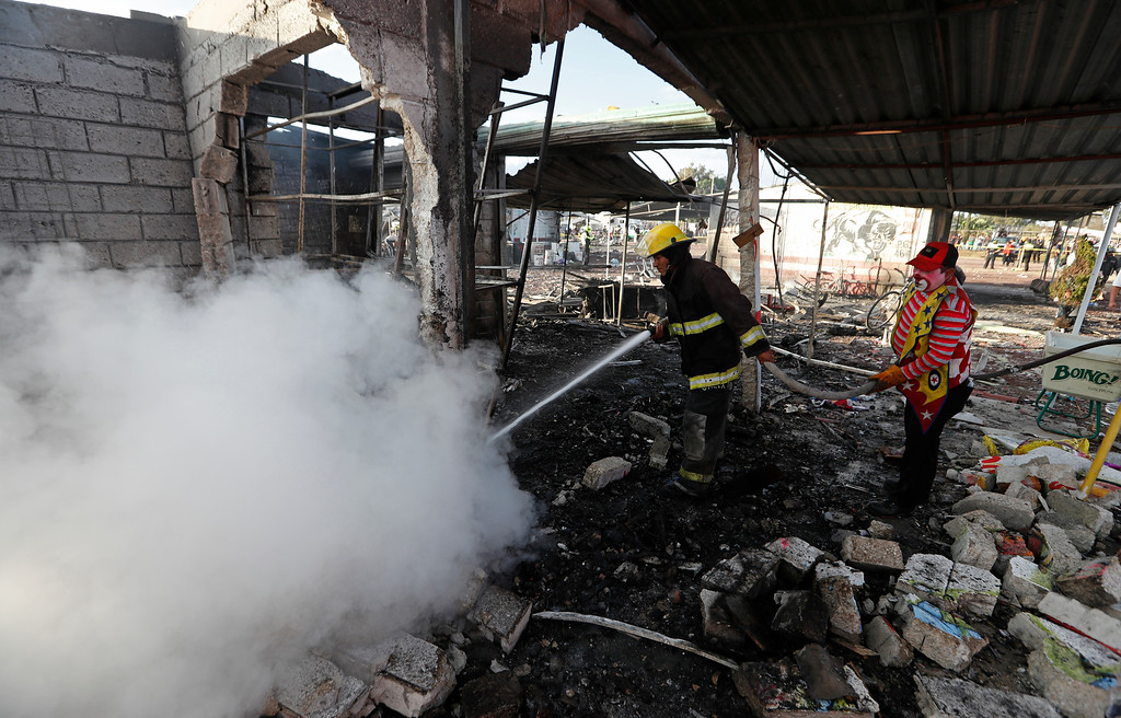 . A local resident dressed as a clown helps a firefighter at the scorched ground of Mexico\'s best-known fireworks market after an explosion explosion ripped through it, inTultepec, Mexico, Tuesday, Dec. 20, 2016. National Civil Protection Coordinator Luis Felipe Puente told Milenio TV that dozens were hurt but he had no immediate report of any fatalities at the open-air San Pablito Market in Tultepec, in the State of Mexico. (AP Photo/Eduardo Verdugo)