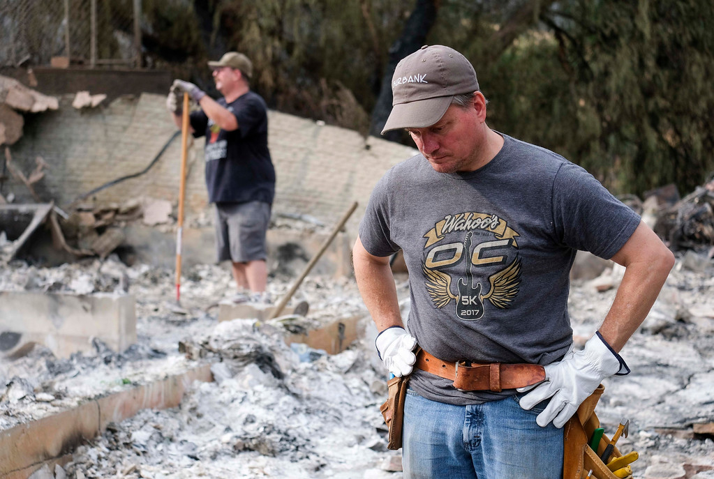 . Craig Bolleson surveys the charred debris left in his burned out home, Monday, Sept. 4, 2017, in the Sunland-Tujunga section of Los Angeles.Wildfires forced thousands to flee their homes across the U.S. West during a sweltering, smoke-shrouded holiday weekend of record heat. (AP Photo/Ringo H.W. Chiu)
