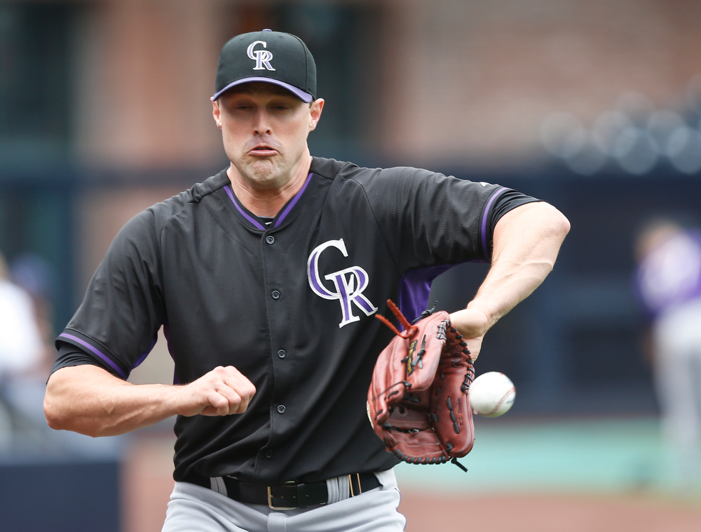 . Colorado Rockies relief pitcher Matt Belisle sidesteps a ball while catching a throw from teammate Michael Cuddyer as the Rockies prepare for a baseball game against the San Diego Padres on Thursday, April 17, 2014, in San Diego.  (AP Photo/Lenny Ignelzi)