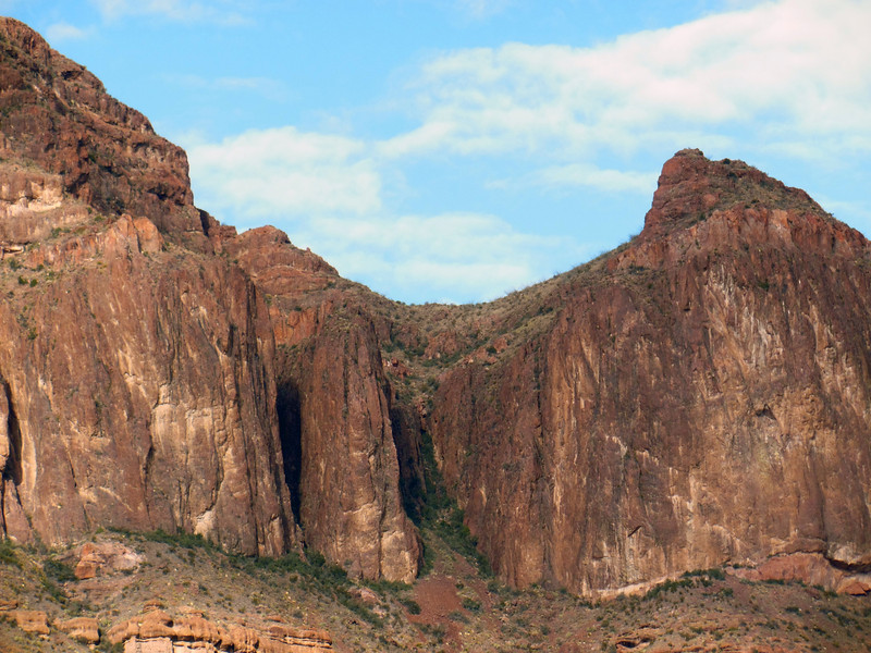 Telephoto shot of the two clefts mentioned previously.  The possible pour-off / chockstone in the main cleft is visible.  In the same cleft there is a southern branch (to climber's left) which is completely hidden in this image, but looks possible on Google Earth.  The narrow cleft to the left doesn't look anymore possible here than in the previous images, but it just calls me!