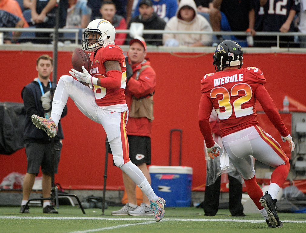 . AFC cornerback Casey Hayward (26), of the Los Angeles Chargers, intercepts a pass, during the second half of the NFL Pro Bowl football game against the NFC, Sunday, Jan. 28, 2018, in Orlando, Fla. To the right is free safety Eric Weddle (32), of the Baltimore Ravens. (AP Photo/Phelan M Ebenhack)
