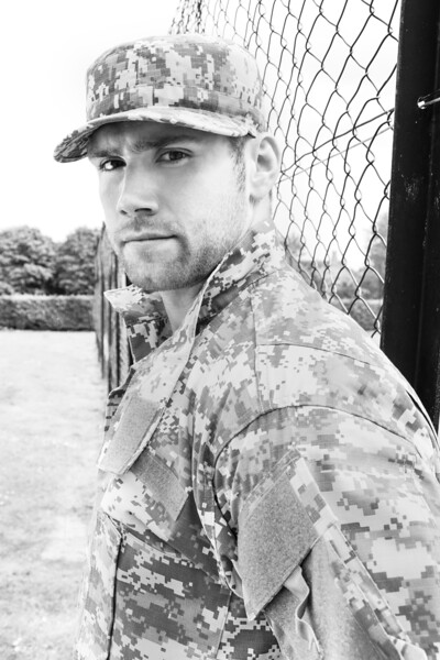 Marine, soldier in his army fatigues stands to attention at military base