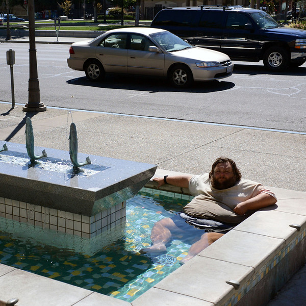 A homeless man named Jasper sits in the fish fountain to wash himself next to the City Council Chambers Wednesday, September 18, 2013, in Chico, Calif. He said many people may think it's disgusting, but it's what he has to do to stay in good hygiene.  (Jason Halley/Chico Enterprise-Record)