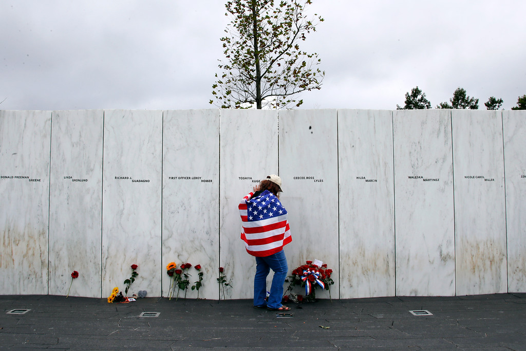. Chrissy Bortz of Latrobe, Pa., pays her respects at the Wall of Names at the Flight 93 National Memorial in Shanksville, Pa. after a Service of Remembrance Tuesday, Sept. 11, 2018, as the nation marks the 17th anniversary of the Sept. 11, 2001 attacks. The Wall of Names honor the 40 people killed in the crash of Flight 93. (AP Photo/Gene J. Puskar)