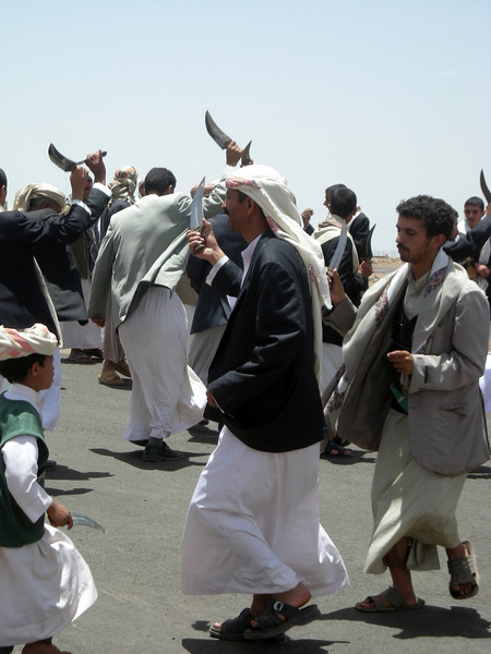 celebrating a wedding, men sing and dance with their jambiyas / knives around the groom, in the village of Kawkaban