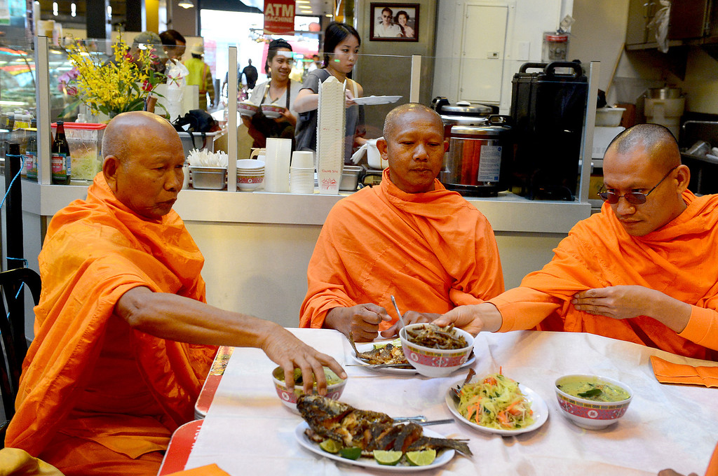 . After blessing the opening of Sticky Rice at Grand Central Market in downtown Los Angeles Monday, April 30, 2013 Wat Thai Temple monks, of North Hollywood, are served their food. Sticky Rice, owned by David Tewasart, of Pasadena, is kicking off the openings of new restaurants at the market. (SGVN/Staff Photo by Sarah Reingewirtz)
