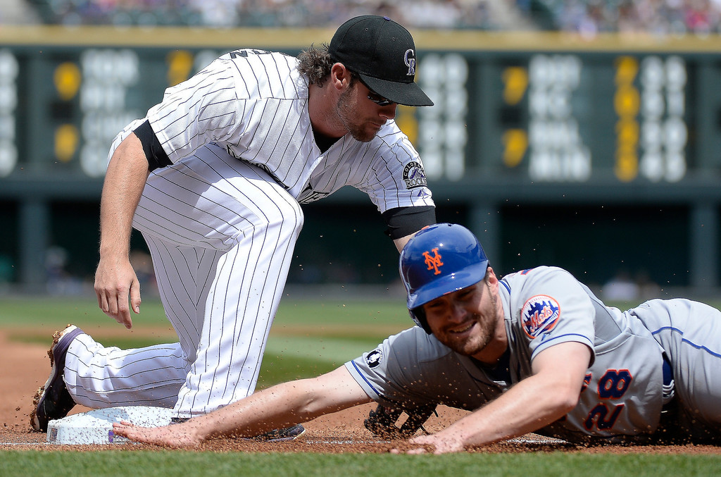 . Colorado Rockies shortstop Charlie Culberson (23) tags New York Mets second baseman Daniel Murphy (28) for double him up for the third out in the first inning on a throw from Colorado Rockies third baseman Nolan Arenado (28) May 4, 2014 at Coors Field. (Photo by John Leyba/The Denver Post)