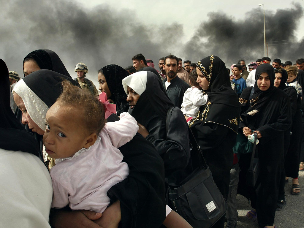 . In this Sunday, March 30, 2003 file photo, Iraqi women line up for a security check by British soldiers on the outskirts of Basra, as they try to flee from this southern Iraqi town. (AP Photo/Anja Niedringhaus, File)