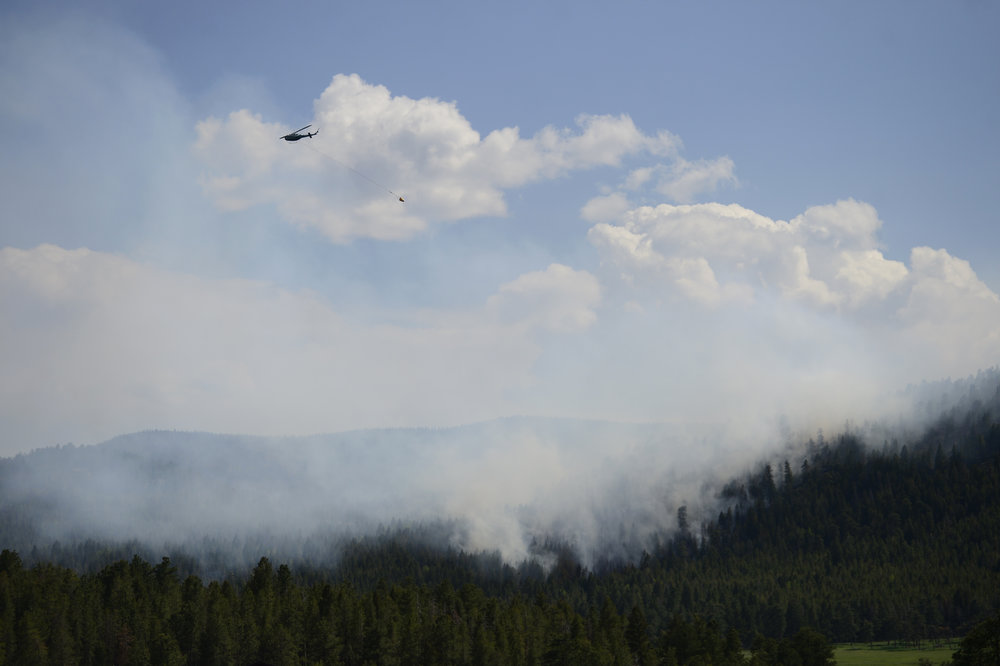 . A helicopter drops water on a fire burning in the hills west of Evergreen, Colorado. A fire started early in the afternoon on June 3, 2013 and by 3:30 p.m., residents of the surrounding area were told to evacuate. Many packed horses and other animals into trailers and drove them to nearby meadows. (Photo by AAron Ontiveroz/The Denver Post)