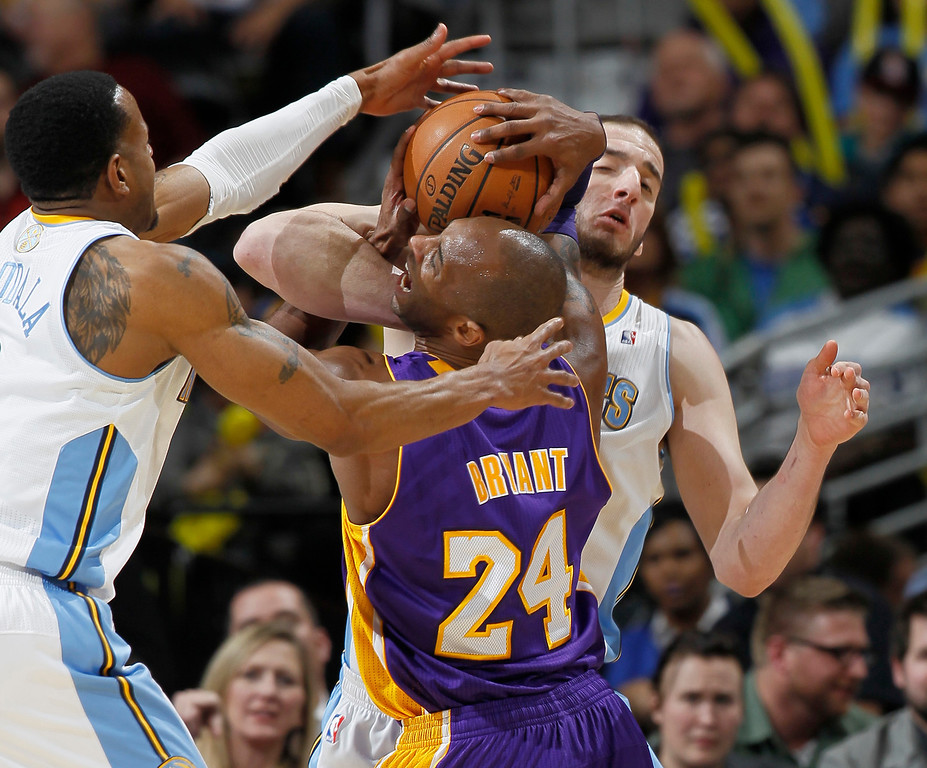 . Los Angeles Lakers guard Kobe Bryant, front right, is fouled while driving for a shot by Denver Nuggets center Kosta Koufos, back right, as guard Andre Iguodala comes in to cover in the third quarter of the Nuggets\' 119-108 victory in an NBA basketball game in Denver on Monday, Feb. 25, 2013. (AP Photo/David Zalubowski)