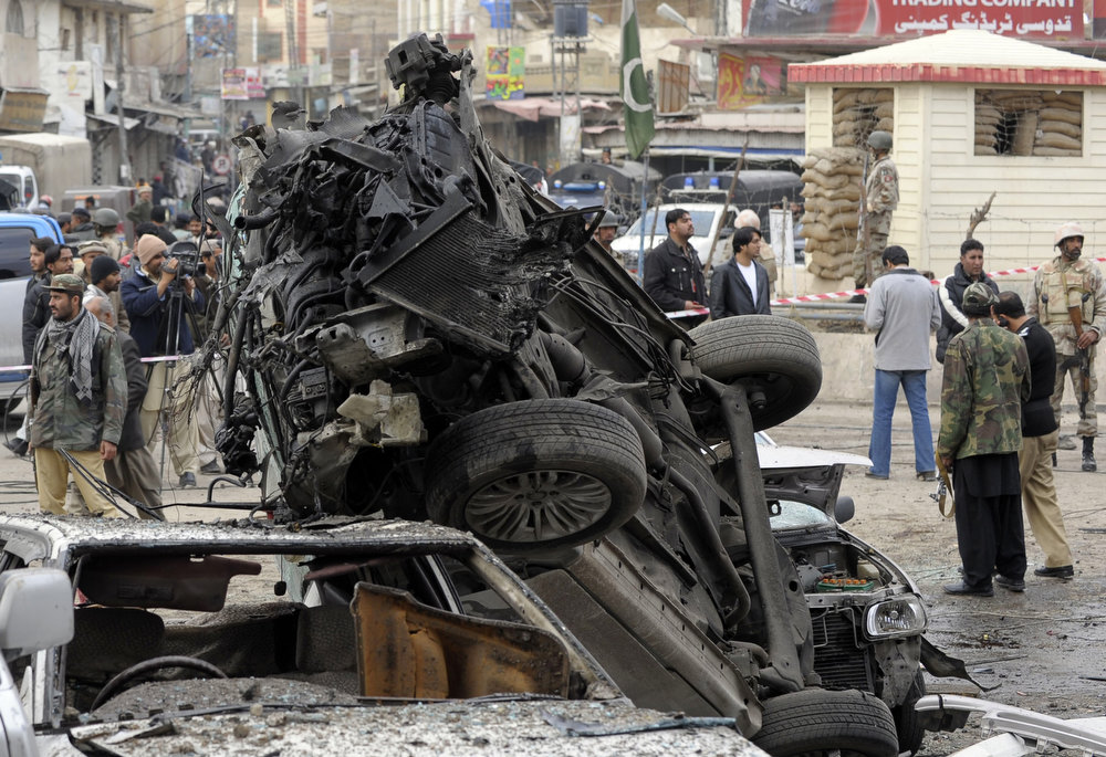 Description of . Pakistani security personnel (background) cordon off the site of a bomb explosion in Quetta on January 10, 2013. A bomb attack killed 11 people and wounded dozens more in a crowded part of Pakistan's southwestern city of Quetta, police said. AFP PHOTO/Banaras  KHAN/AFP/Getty Images