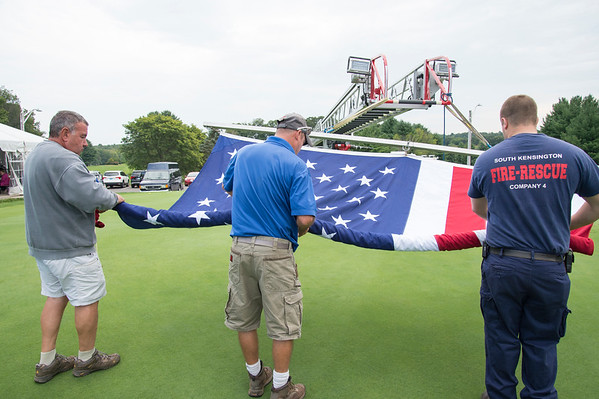 09/11/19 Wesley Bunnell | StaffrrCCARC held their annual golf tournament on Wednesday September 11, 2019 at Timberlin Golf Club in Berlin. Members of the Berlin Fire Department prepare to take down a large american flag which was present for the CCARC 9/11 tribute before the start of the tournament.