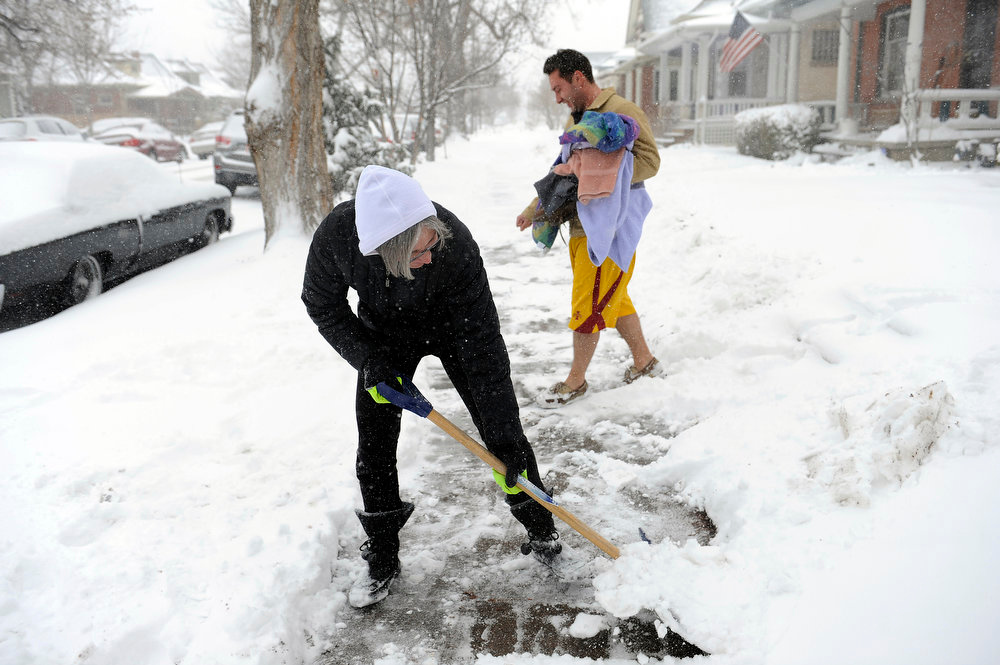 . Mary Dulacki clears snow off a sidewalk as Charles Owen makes his way to his vehicle on S. Washington St in Denver on Sunday, February, 24, 2013. Seth A. McConnell, The Denver Post
