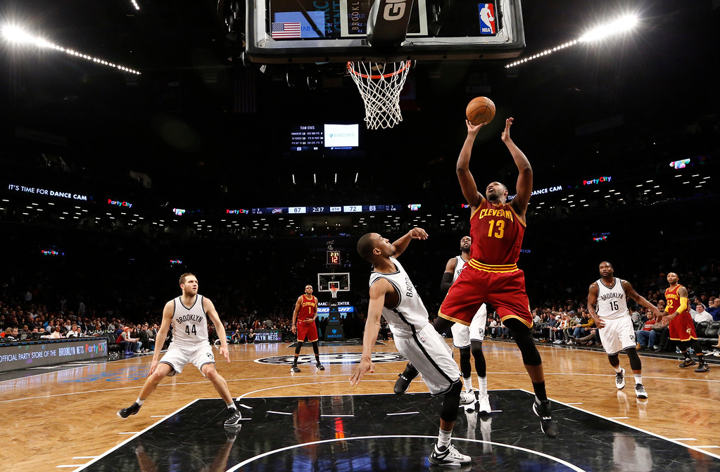 . Cleveland Cavaliers center Tristan Thompson (13) takes a shot in the second half of an NBA basketball game, sending Brooklyn Nets guard Markel Brown (22) to the floor, Wednesday, Jan. 20, 2016, in New York. The Cavaliers defeated the Nets 91-78. (AP Photo/Kathy Willens)