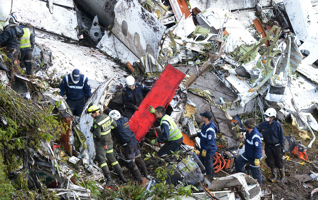 . Rescue workers comb through the wreckage site of an airplane crash, in La Union, a mountainous area near Medellin, Colombia, Tuesday , Nov. 29, 2016. The chartered plane was carrying a Brazilian soccer team to the biggest match of its history when it crashed into a Colombian hillside and broke into pieces, killing 75 people and leaving six survivors, Colombian officials said Tuesday. (AP Photo/Fernando Vergara)