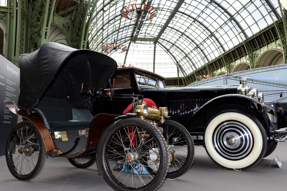 . (Left) A Victoria Combination 2¼hp (1899) is pictured as luxury vintages cars are displayed at an auction at the Grand Palais on February 6, 2013 in Paris. 125 vintage motor cars, 100 collection motorbikes and a 1920\'s Gipsy Moth plane by De Havilland, will be presented at the Bonhams auction on February 7.  BERTRAND GUAY/AFP/Getty Images