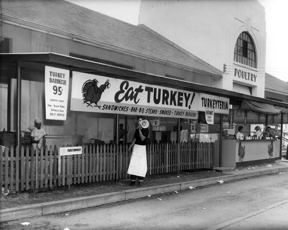 """. A young man holds a megaphone at the \""""Eat Turkey! Turkeyteria\"""" food concession just outside of the Poultry building at the Minnesota State Fair in 1960. Turkey barbecue for $0.95. Photo courtesy of the Minnesota State Fair."""
