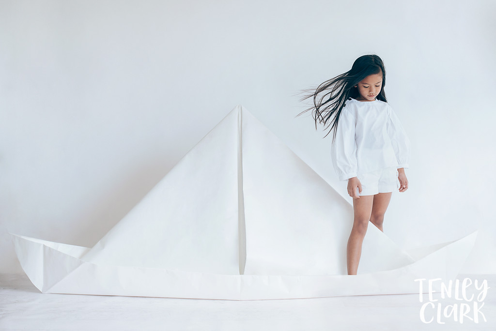 Giant paper boat. Whimsical kid's fashion editorial with giant white paper origami props. Photography by Tenley Clark.