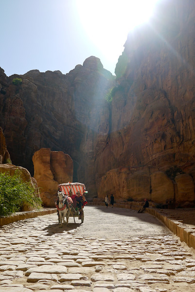 Tourists ride a horse and carriage toward the Treasury in Petra, Jordan.
