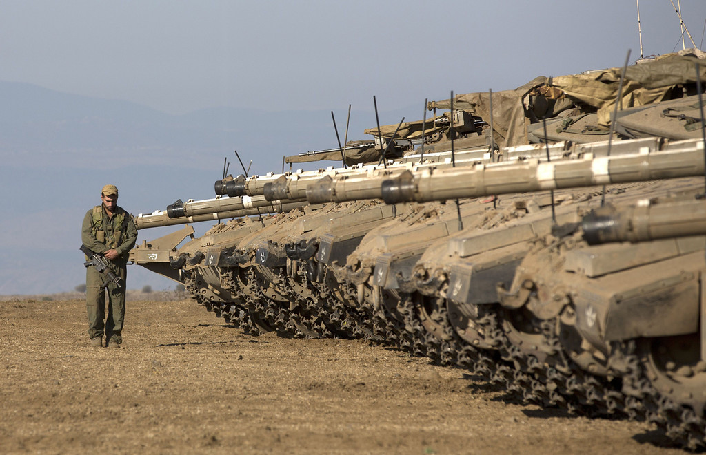 ". An Israeli soldier walks next to Merkava tanks stationed in a deployment training area in the Israeli-annexed Golan Heights near the border with Syria on August 28, 2013. Israel will strike back ""fiercely\"" if Syria attacks the Jewish state, Prime Minister Benjamin Netanyahu said, as the US mulled military action against President Bashar al-Assad\'s regime. MENAHEM KAHANA/AFP/Getty Images"