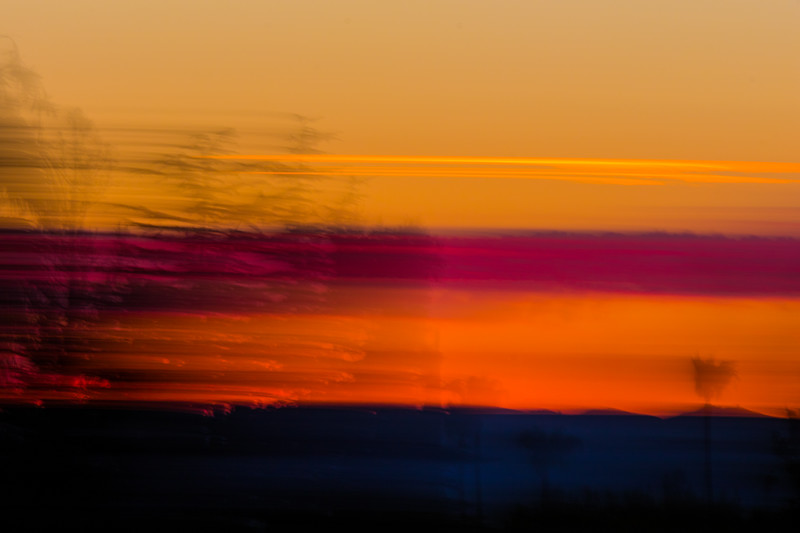 Abstract and fast streaking purple and orange and yellow clouds at sunset in California