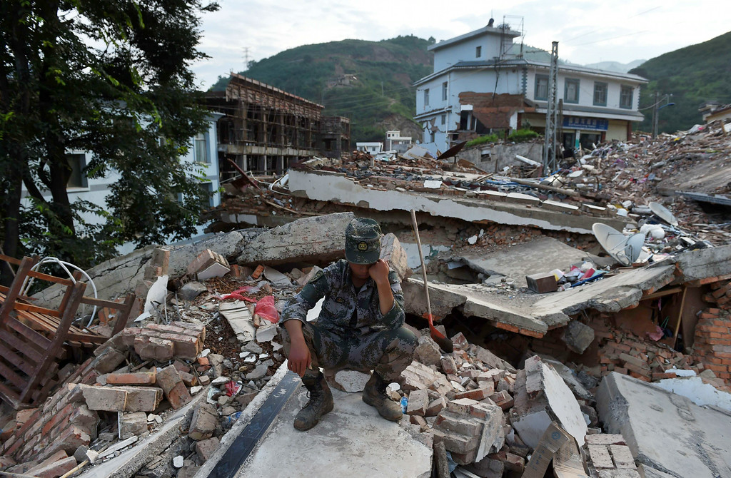 . A paramilitary policeman rests on the roof of a collapsed building after spending the day searching for earthquake victims at Longtoushan, in China\'s southwest Yunnan province on August 5, 2014.   AFP PHOTO/Greg  BAKER/AFP/Getty Images