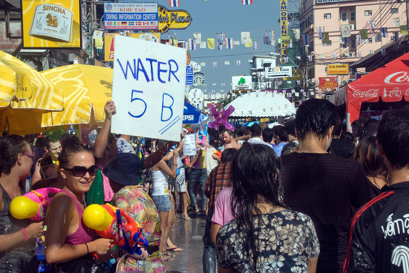 Man holding out sign of water for sale during Songkran Festival