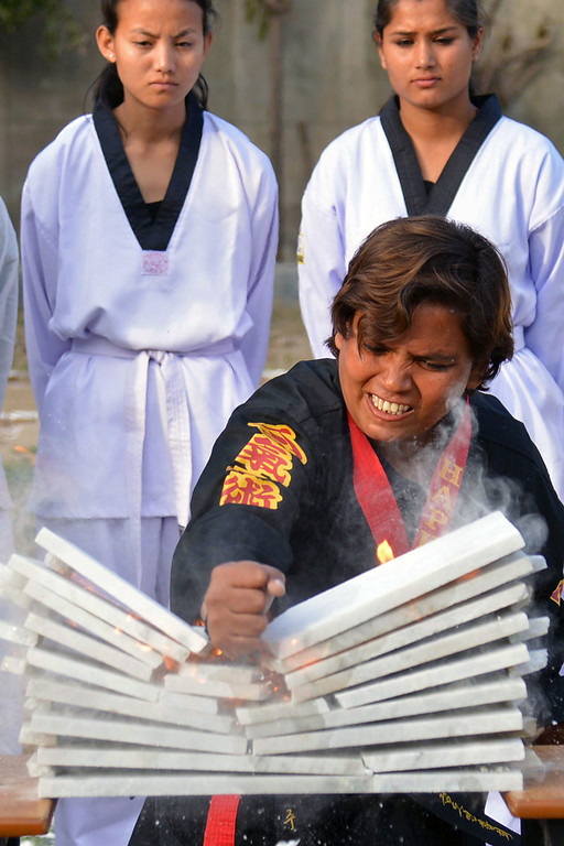 . A female karate exponent demonstrates her skills during International Women\'s Day in Amritsar on March 8, 2014. International Women\'s Day (IWD), originally called International Working Women\'s Day is a global day annually on March 8, celebrating the economic, political and social achievements of women past, present and future. (NARINDER NANU/AFP/Getty Images)