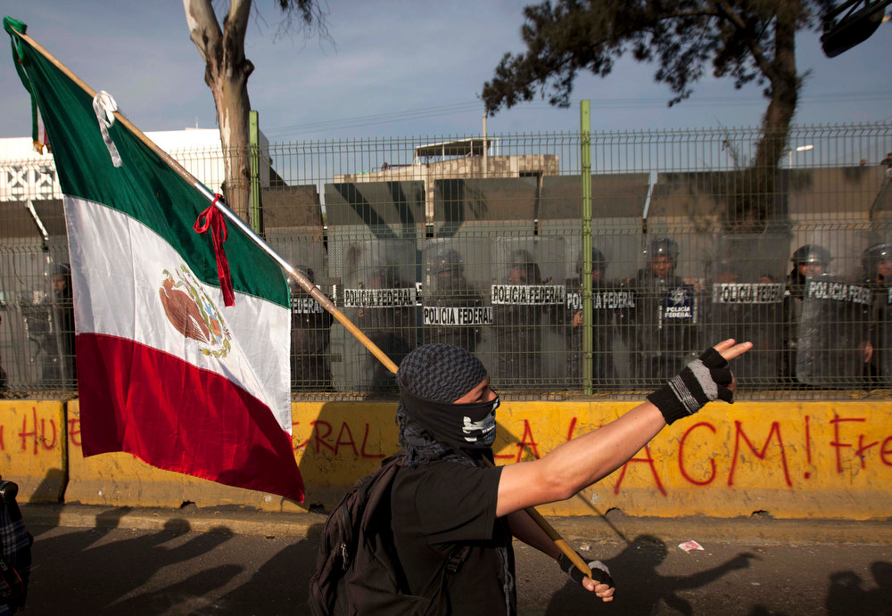 . A demonstrator holds a Mexican flag  during protests against new Mexican President Enrique Pena Nieto\'s rule outside the National Congress,  before he was to take the oath of office in Mexico City, Saturday, Dec. 1, 2012.  Hundreds of protesters banged on the steel security barriers around Congress, threw rocks, bottle rockets and firecrackers at police.  Pena Nieto took power at midnight in a symbolic ceremony and will formally take the oath of office Saturday morning. (AP Photo/Eduardo Verdugo)