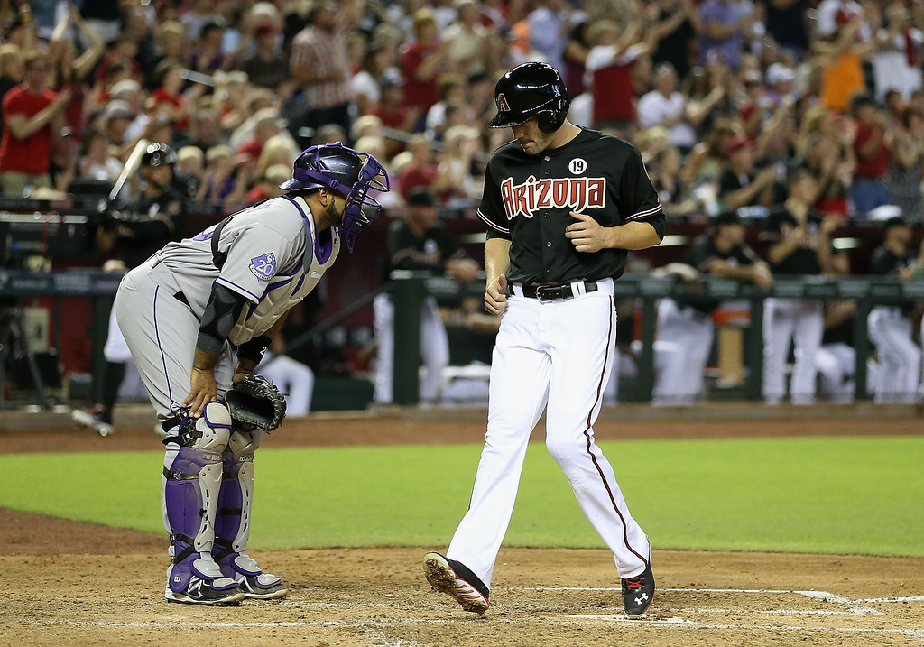 . PHOENIX, AZ - JULY 05:  A.J. Pollock #11 of the Arizona Diamondbacks scores a run past catcher Wilin Rosario #20 of the Colorado Rockies on a single hit by Paul Goldschmidt (not pictured) during the third inning of the MLB game at Chase Field on July 5, 2013 in Phoenix, Arizona.  (Photo by Christian Petersen/Getty Images)
