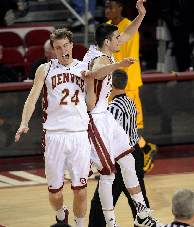 . Denver Pioneers forward Dom Samac (24) and Denver Pioneers guard Brett Olson (23) celebrate their victory over the Wyoming Cowboys 64-61 December 15, 2013 Magness Arena. (Photo by John Leyba/The Denver Post)