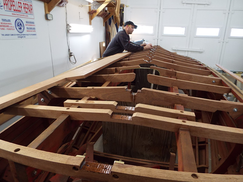 Appling epoxy to the bottom frames before gluing the new keel in place.