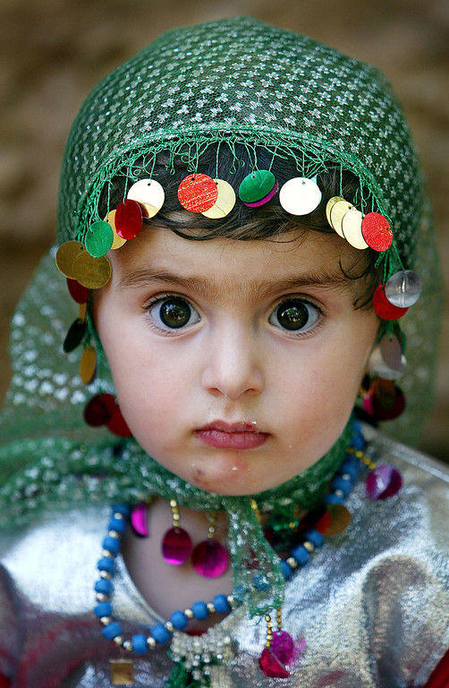 . A Kurdish girl, Leiwan, 2, attends a traditional wedding celebration June 15, 2003 in Bakochek, Iraq. Saddam Hussein\'s regime killed an estimated 180,000 Kurds from 1988-1991 in a genocidal campaign involving both chemical and conventional weapons. (Photo by Mario Tama/Getty Images)