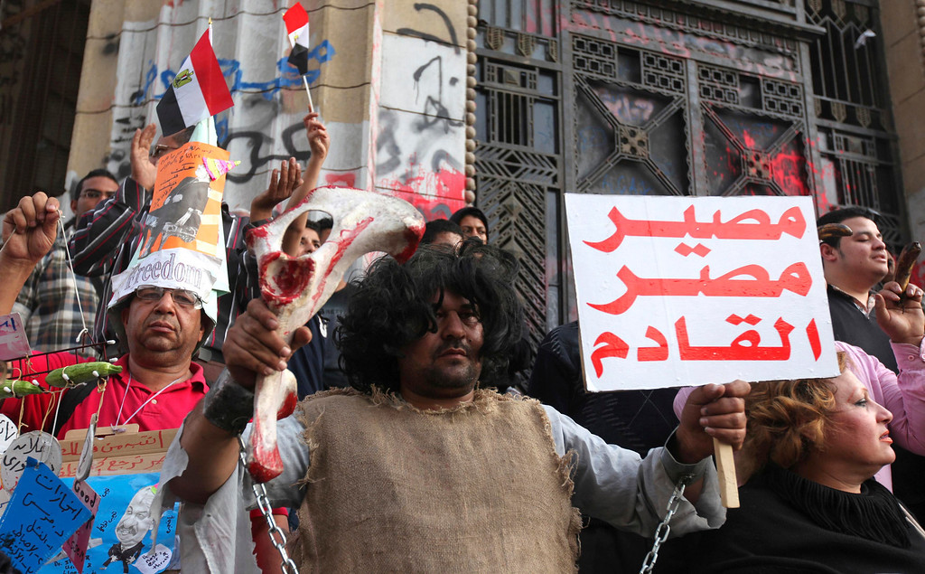". An activist, dressed as a chained prehistoric man, stands with anti-Mursi demonstrators and members of the 6th of April activist movement in front of the High Court during a rally in Cairo April 6, 2013. The movement calls for a \'Day of Rage\' to protest against the arrest of activists and the stifling of free expression. The movement was one of the key players in the uprising that toppled former President Hosni Mubarak. The banner reads, ""Egypt future\"".   REUTERS/Mohamed Abd El Ghany"