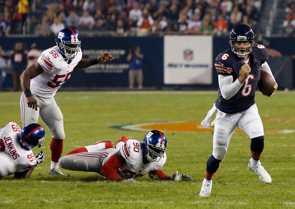 . Chicago Bears quarterback Jay Cutler (6) scrambles past New York Giants defenders Cullen Jenkins (99), Keith Rivers (55) and Jason Pierre-Paul (90) in the first half of an NFL football game, Thursday, Oct. 10, 2013, in Chicago. (AP Photo/Charles Rex Arbogast)