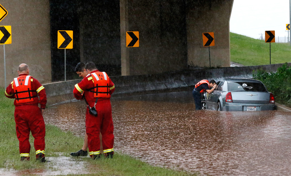 . A firefighter looks into the window of a partially submerged car, checking to see if anyone is inside, Saturday, May 23, 2015, in Oklahoma City. The Oklahoma Department of Transportation said at least 15 highways have been closed across the state due to high water from the recent flooding. (Jim Beckel/The Oklahoman via AP) LOCAL STATIONS OUT (KFOR, KOCO, KWTV, KOKH, KAUT OUT); LOCAL WEBSITES OUT; LOCAL PRINT OUT (EDMOND SUN OUT, OKLAHOMA GAZETTE OUT) TABLOIDS OUT