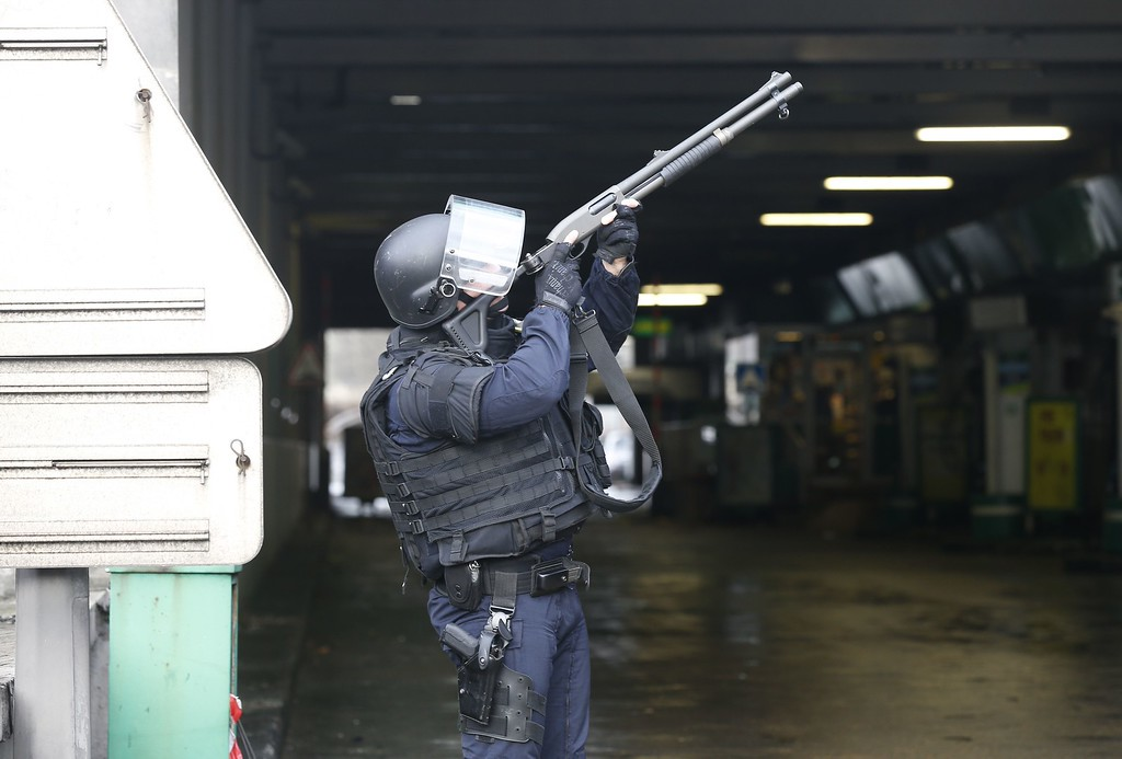 . A member of the police force aims as he mans a position at Porte de Vincennes, eastern Paris, after at least one person was injured when a gunman opened fire at a kosher grocery store on January 9, 2015 and took at least five people hostage, sources told AFP. The attacker was suspected of being the same gunman who killed a policewoman in a shooting in Montrouge in southern Paris on January 8.     AFP PHOTO / THOMAS  SAMSON/AFP/Getty Images
